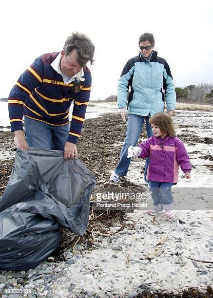 Derrick Daly left head gardener at the Inn By The Sea in Cape Elizabeth holds a bag open for two yearold Kate Hetrick to throw away trash as her...