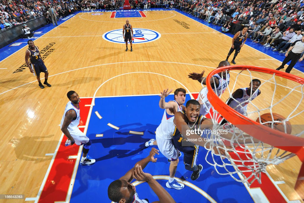 Derrick Favors #15 of the Utah Jazz drives to the basket against Spencer Hawes #00 of the Philadelphia 76ers at the Wells Fargo Center on November 16, 2012 in Philadelphia, Pennsylvania.