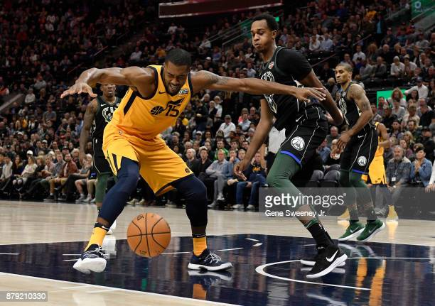 Derrick Favors of the Utah Jazz loses the ball while being guarded by John Henson of the Milwaukee Bucks in the first half at Vivint Smart Home Arena...
