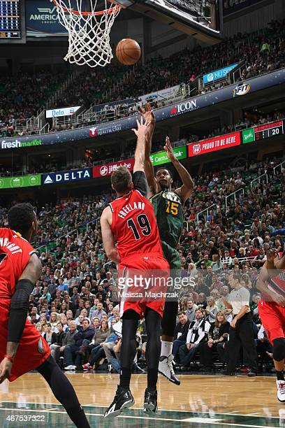Derrick Favors of the Utah Jazz shoots against Joel Freeland of the Portland Trail Blazers on March 25 2015 at EnergySolutions Arena in Salt Lake...