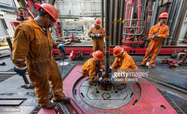 Derrick hands remove the drilling tool with a sample of the marine seabed at La Muralla IV exploration oil rig operated by Mexican company 'Grupo R'...