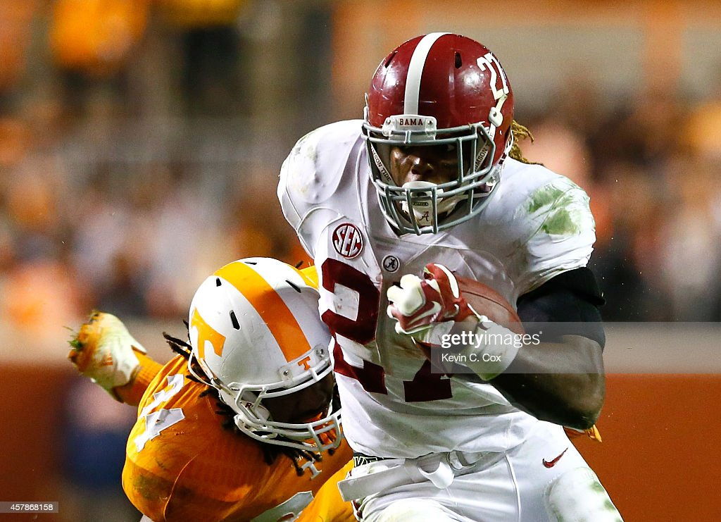 Derrick Henry #27 of the Alabama Crimson Tide breaks a tackle by Jalen Reeves-Maybin #34 of the Tennessee Volunteers at Neyland Stadium on October 25, 2014 in Knoxville, Tennessee.