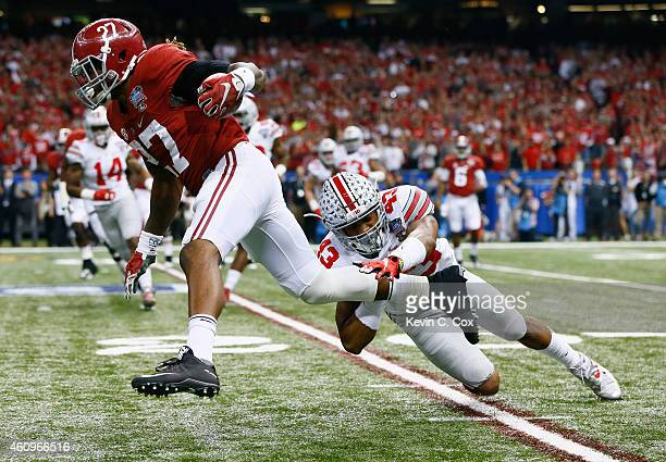 Derrick Henry of the Alabama Crimson Tide runs the ball in the first quarter against Darron Lee of the Ohio State Buckeyes during the All State Sugar...