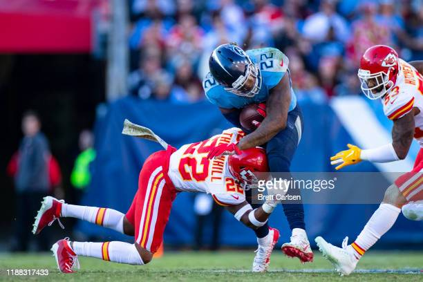 Derrick Henry of the Tennessee Titans absorbs a hit by Juan Thornhill of the Kansas City Chiefs on his way to a first down during the fourth quarter...