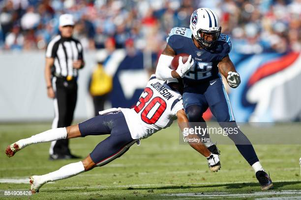 Derrick Henry of the Tennessee Titans breaks a tackle from Kevin Johnson of the Houston Texans during the first half at Nissan Stadium on December 3...