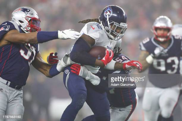 Derrick Henry of the Tennessee Titans carries the ball against Dont'a Hightower of the New England Patriots in the second quarter of the AFC Wild...