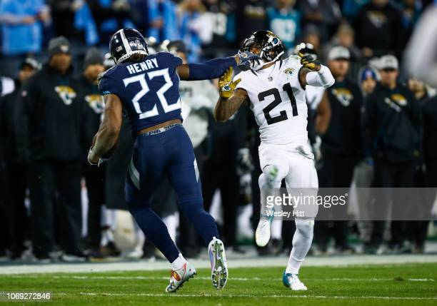 Derrick Henry of the Tennessee Titans fends off defender AJ Bouye of the Jacksonville Jaguars while running with the ball during the second quarter...