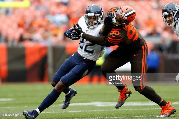 Derrick Henry of the Tennessee Titans grabs the face mask of Myles Garrett of the Cleveland Browns while fighting for positive yards during the...