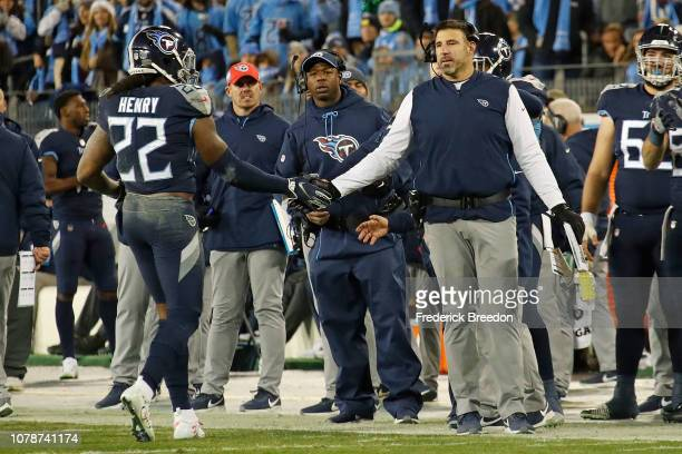 Derrick Henry of the Tennessee Titans high fives head coach Mike Vrabel as he leaves the field after breaking the franchise record for yards in a...