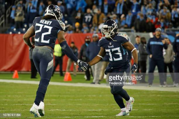 Derrick Henry of the Tennessee Titans high fives teammate Dion Lewis as he leaves the field after breaking the franchise record for yards in a game...