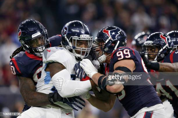 Derrick Henry of the Tennessee Titans is tackled by J.J. Watt of the Houston Texans and Jadeveon Clowney in the fourth quarter at NRG Stadium on...
