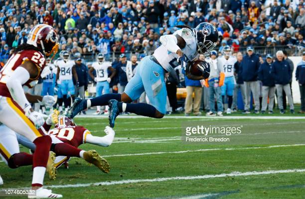 Derrick Henry of the Tennessee Titans is tripped by Ha Ha ClintonDix of the Washington Redskins while running to score a touchdown during the first...