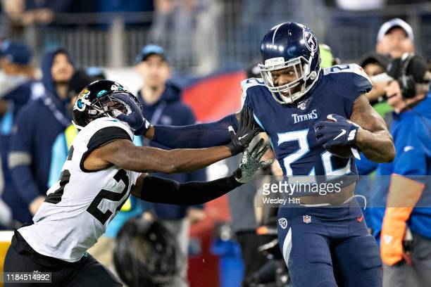 Derrick Henry of the Tennessee Titans runs for a touchdown in the second half and stiff arms Jarrod Wilson of the Jacksonville Jaguars at Nissan...