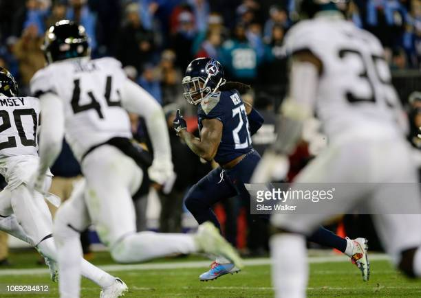Derrick Henry of the Tennessee Titans runs past Jacksonville Jaguars defenders with the ball during the fourth quarter at Nissan Stadium on December...