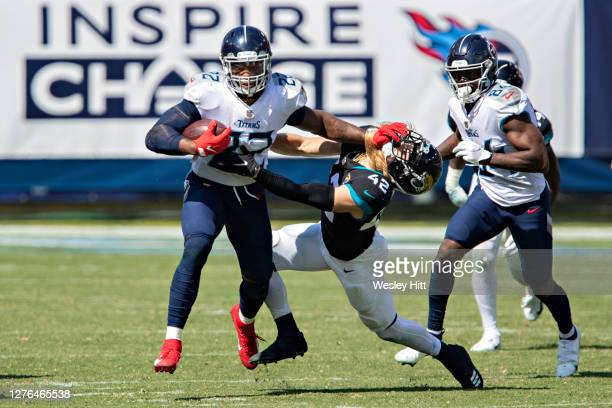 Derrick Henry of the Tennessee Titans runs the ball and stiff arms Andrew Wingard of the Jacksonville Jaguars at Nissan Stadium on September 20, 2020...