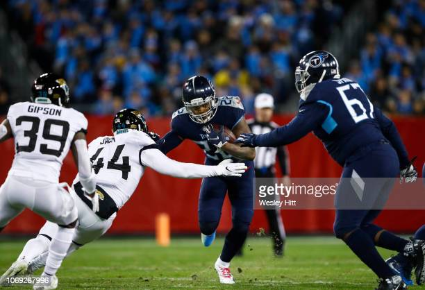 Derrick Henry of the Tennessee Titans runs with the ball while defended by Myles Jack of the Jacksonville Jaguars during the first quarter at Nissan...