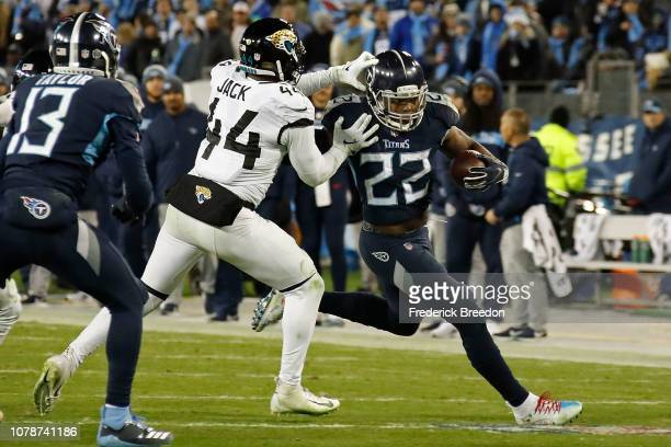 Derrick Henry of the Tennessee Titans rushes against Myles Jack of the Jacksonville Jaguars at Nissan Stadium on December 6 2018 in Nashville...