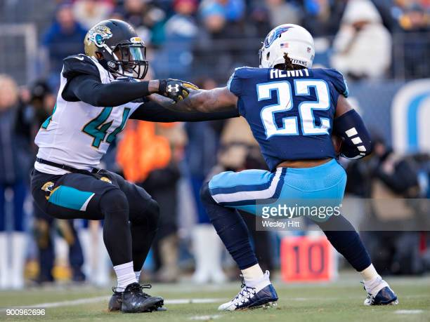 Derrick Henry of the Tennessee Titans stiff arms and breaks away from Myles Jack of the Jacksonville Jaguars at Nissan Stadium on December 31 2017 in...