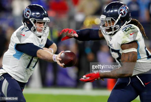 Derrick Henry of the Tennessee Titans takes the hand off from quarterback Ryan Tannehill during the AFC Divisional Playoff game against the Baltimore...