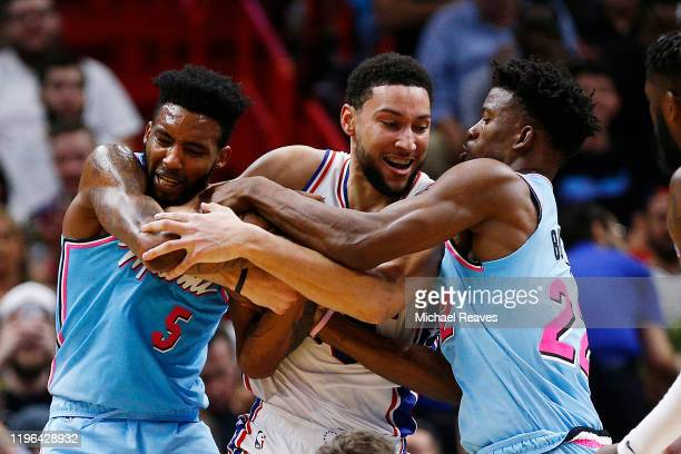 Derrick Jones Jr #5 and Jimmy Butler of the Miami Heat battles for a loose ball with Ben Simmons of the Philadelphia 76ers during the first half at...