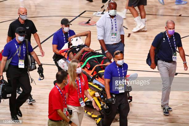 Derrick Jones Jr. #5 of the Miami Heat covers his face with a towel while he is taken off the court by medical personnel after colliding with Goga...