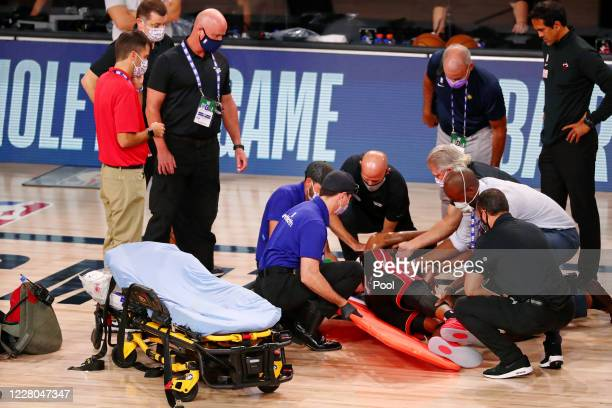 Derrick Jones Jr. #5 of the Miami Heat is tended to by medical personnel after colliding with Goga Bitadze of the Indiana Pacers during the second...