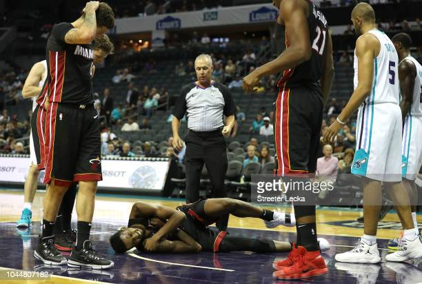 Derrick Jones Jr #5 of the Miami Heat reacts after hitting the floor causing him to leave the game against the Charlotte Hornets during their game at...