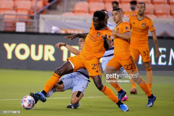 Derrick Jones of Houston Dynamo steals the ball from Alan Pulido of Sporting Kansas City during the first half at BBVA Stadium on May 12, 2021 in...