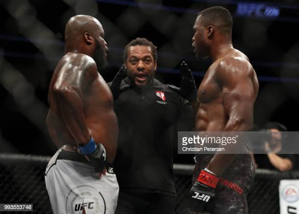 Derrick Lewis and Francis Ngannou of Cameroon take instruction from Herb Dean in their heavyweight fight during the UFC 226 event inside TMobile...
