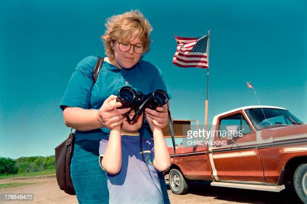 Derrick Lupher of Waco Texas gets help from his aunt Patty with binoculars on a hill near the Branch Davidian cult compound on April 09 while the two...