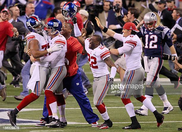 Derrick Martin and the New York Giants celebrate in front of Tom Brady of the New England Patriots after defeating the New England Patriots by a...