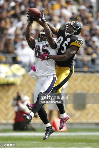 Derrick Mason of the Baltimore Ravens catches a first quarter pass in front of Ryan Clark of the Pittsburgh Steelers on October 3 2010 at Heinz Field...