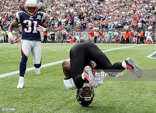 Derrick Mason of the Baltimore Ravens rolls over in the endzone after making a touchdown catch as Brandon Meriweather of the New England Patriots on...