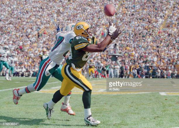 Derrick Mayes Wide Receiver for the Green Bay Packers catching the ball from Defensive Back Terrell Buckley of the Miami Dolphins during the National...