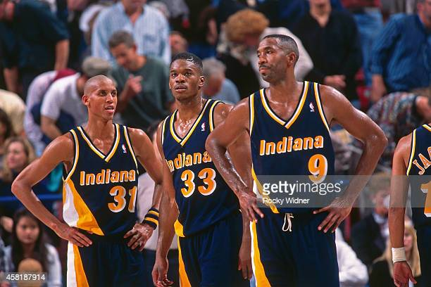 Derrick McKey Reggie Miller and Antonio Davis of the Indiana Pacers stand against the Sacramento Kings on November 30 1995 at Arco Arena in...