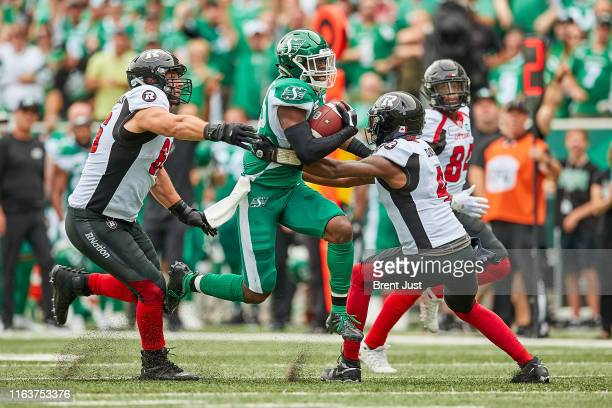 Derrick Moncrief of the Saskatchewan Roughriders runs with the ball through Nolan MacMillan and Dominique Davis of the Ottawa RedBlacks after...