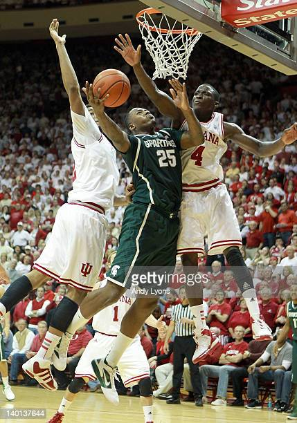 Derrick Nix of the Michigan State Spartans shoots the ball while defended by Christian Watford and Victor Oladipo of the Indiana Hoosiers during the...