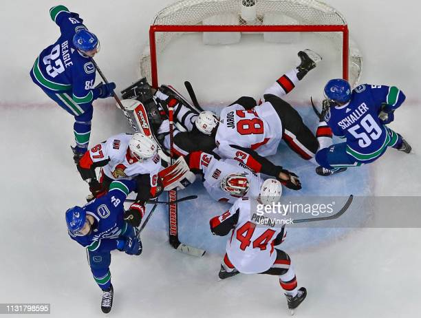 Derrick Pouliot and Tim Schaller of the Vancouver Canucks look on as Anders Nilsson of the Ottawa Senators makes a save during their NHL game at...