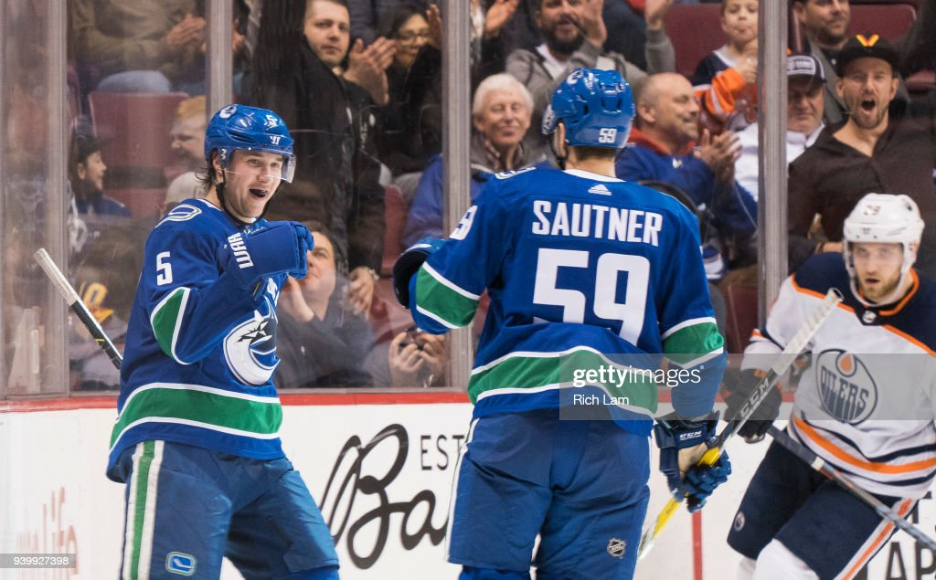 Derrick Pouliot #5 of the Vancouver Canucks celebrates with Ashton Sautner #59 after scoring what proved to be the game winning goal against the Edmonton Oilers in NHL action on March, 29, 2018 at Rogers Arena in Vancouver, British Columbia, Canada.