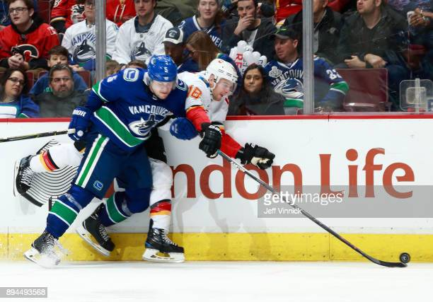 Derrick Pouliot of the Vancouver Canucks checks Matt Stajan of the Calgary Flames into the boards during their NHL game at Rogers Arena December 17...