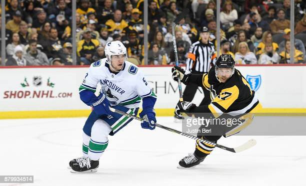 Derrick Pouliot of the Vancouver Canucks skates against Bryan Rust of the Pittsburgh Penguins in the second period during the game at PPG PAINTS...