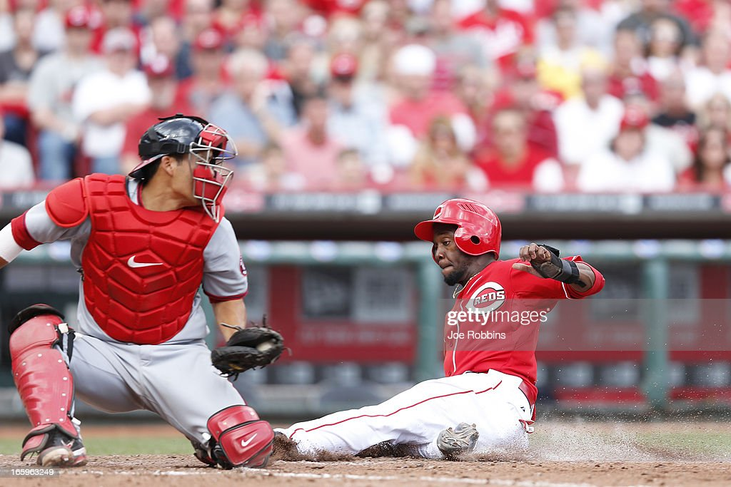 Derrick Robinson #15 of the Cincinnati Reds slides at home plate to score the go-ahead run in the sixth inning of the game against the Washington Nationals at Great American Ball Park on April 7, 2013 in Cincinnati, Ohio. The Reds won 6-3.