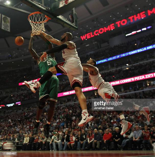 Derrick Rose and Carlos Boozer of the Chicago Bulls leap to block a shot by Kevin Garnett of the Boston Celtics at United Center on April 7 2011 in...