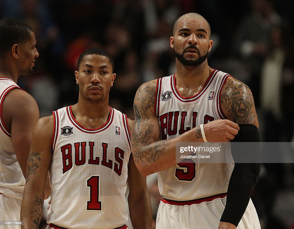 Derrick Rose #1 and Carlos Boozer #5 of the Chicago Bulls return to the court after a time-out against the San Antonio Spurs at the United Center on February 17, 2011 in Chicago, Illinois. The Bulls defeated the Spurs 109-99.