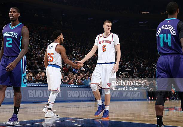 Derrick Rose and Kristaps Porzingis of the New York Knicks high five during the game against the Charlotte Hornets at Madison Square Garden in New...