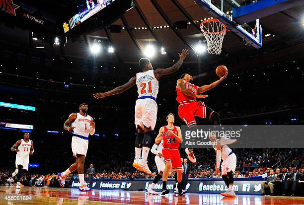 Derrick Rose of the Chicago Bulls attempts a layup under Iman Shumpert of the New York Knicks in the second quarter during a game at Madison Square...