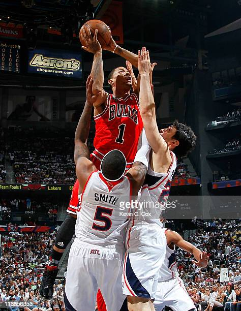 Derrick Rose of the Chicago Bulls drives against Josh Smith and Zaza Pachulia of the Atlanta Hawks in Game Four of the Eastern Conference Semifinals...