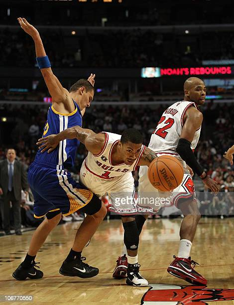 Derrick Rose of the Chicago Bulls drives between teammate Taj Gibson and Andris Biedrins of the Golden State Warriors at the United Center on...