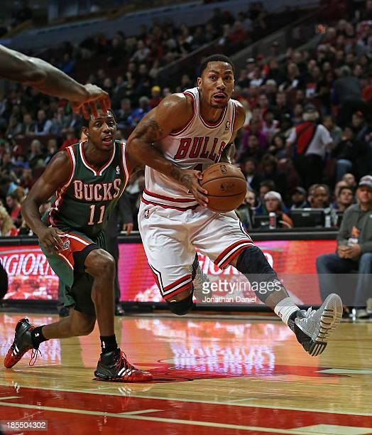 Derrick Rose of the Chicago Bulls drives past Brandon Knight of the Milwuakee Bucks during a preseason game at the United Center on October 21 2013...