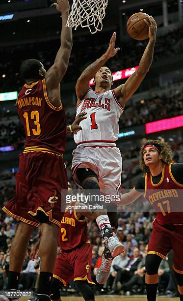 Derrick Rose of the Chicago Bulls drives to the basket between Tristan Thompson and Anderson Varejao of the Cleveland Cavaliers at the United Center...